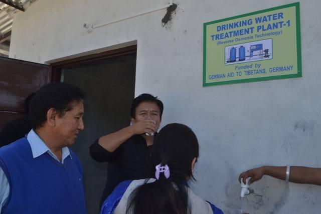 Lehrer trinken Wasser aus der neuen Trinkwasseranlage