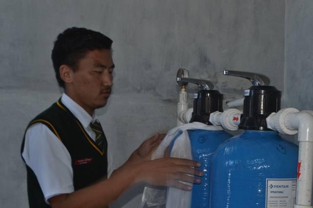 blaue Trinkwasserbehälter werden mit Schals geschmückt