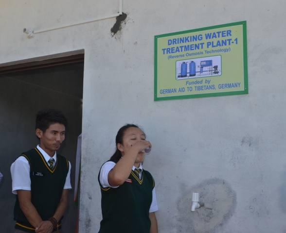Mädchen trinkt frisches Wasser aus Wasserhahn