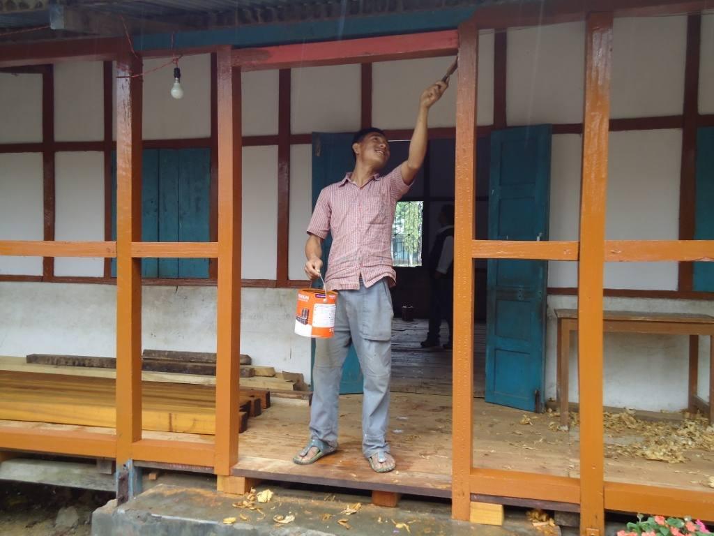 Mann streicht Holz auf der Terrasse der erweiterten Zahnklinik in Miao