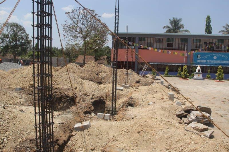 Baubeginn Sambhota Schule Bylakuppe Stahlstützen in Baugrube
