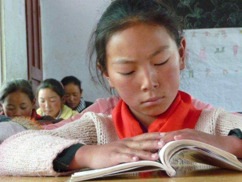Eine tibetische Schülerin beim Lesen
